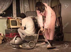 Ретро домохозяйка в ее халате и тапочках очистки грязной гостиной со старин...