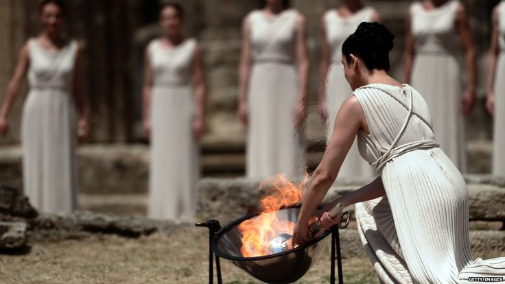 At the lighting ceremony of the Olympic flame, actress Ino Menegaki played the key role of the high priestess. Using a parabolic mirror - and a little olive oil - she captured the morning sun's rays to ignite the Olympic flame. The ceremony took place at the Temple of Hera, Greece, where the flame is kindled for every Olympics.