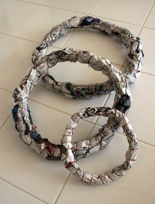 Christmas wreaths get their form from newspaper. This tutorial then covers them in paper streamers...I'm thinking spray paint?