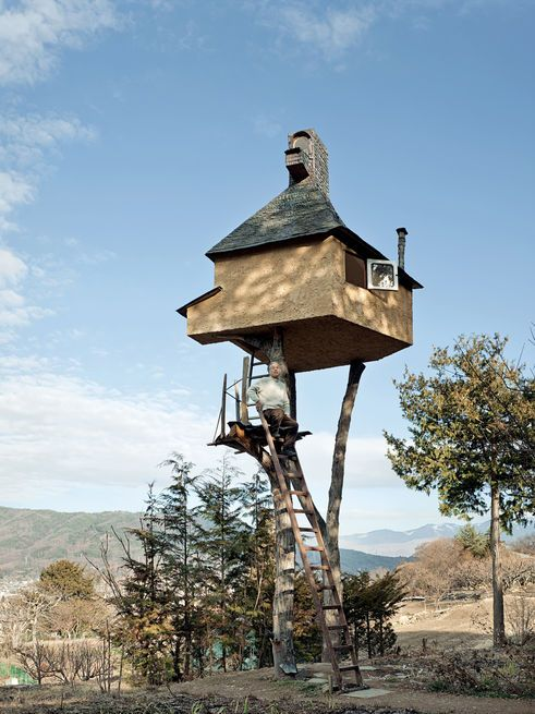 """Fujimori's retreat in Nagano, The Too-High Tea House, which is adorned with a roof of hand-rolled copper sheets, seems precariously perched atop a pair of tree trunks 20 feet in the sky. Why two? """"One leg is dangerous and three legs are too stable and boring.""""  Photo by: Adam Friedberg"""