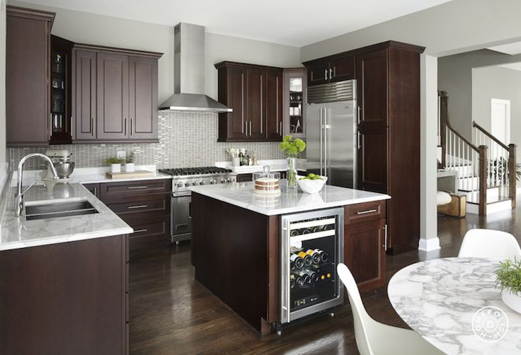 Contemporary kitchen features dark brown cabinets paired with white marble countertops and a gray ...