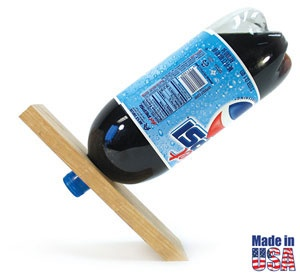 A fascinating conversation piece that illustrates the principle of center of gravity! A small hole in an oak board allows you to balance a 2-liter soda bottle at an angle that appears to defy gravity.