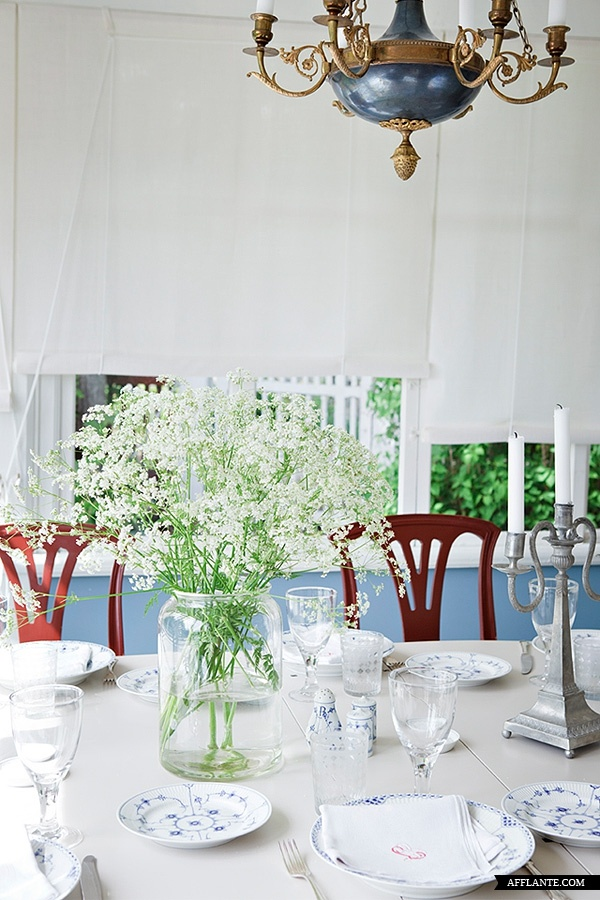 A Swedish summer house is designed around the dining table where family and friends come together to enjoy the flavors of the season. Here the table is set with simple grace that invites us to do nothing more than enjoy. The hint of red on the monogramed napkins . . . . Scrumptious!