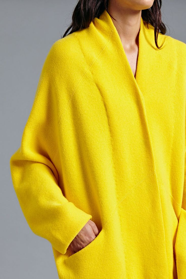 Leena Cashmere Coat In Yellow. This knitted cashmere coat is made from supremely soft fibres. It features a 'pod-like' silhouette with a draped shoulder construction. There is a subtle pocket on either side at waist level.