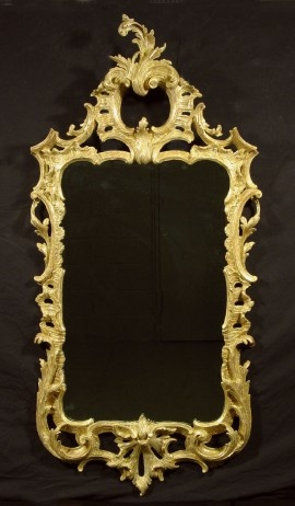 "A George II Giltwood Mirror,     CIRCA 1750,     Height: 60 1/2"" Width: 30"".       The rectangular plate within a conforming surround exuberantly carved with C-scrolls, foliate sprays, and pierced cabochon, surmounted by a foliate C-scroll clasp."