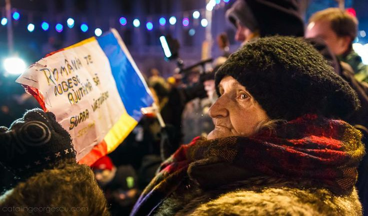 """December 21, 2000 people march on the main street downtown Bucharest, Romania, to commemorate 24 years since the Romanian Revolution took place. An old woman holds sign saying """"Romania I love you, help me survive"""""""