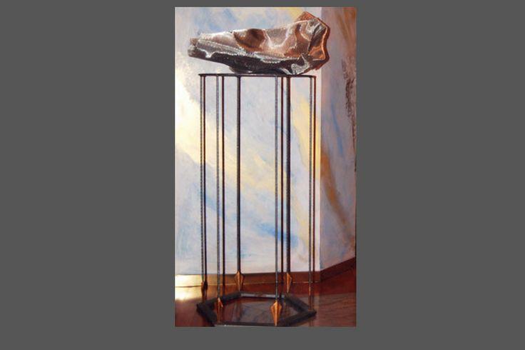Tavolino rotondo in ferro con frecce e supporto in lamiera a quadri.