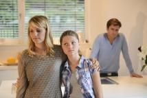 Mid adult woman with arm around daughter and father in the background - altrendo images/Stockbyte/Getty Images