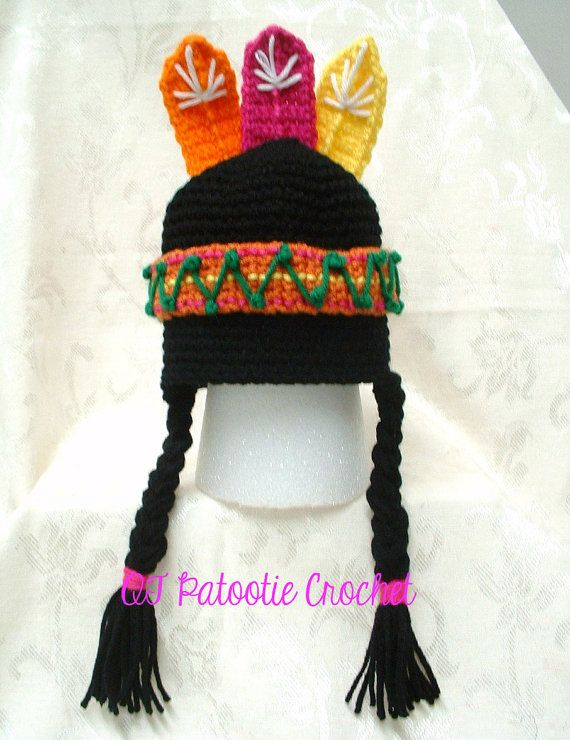 A sweet little Indian Girl Hat crocheted in black with a headband in a rusty color with accents of yellow, magenta in straight rows around the