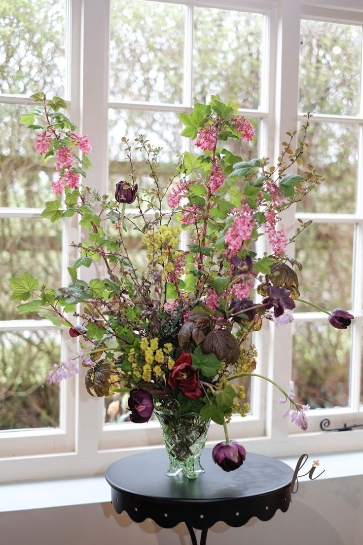 Tulips, euphorbia, berberis and ribes secured by chicken wire in a vintage glass vase