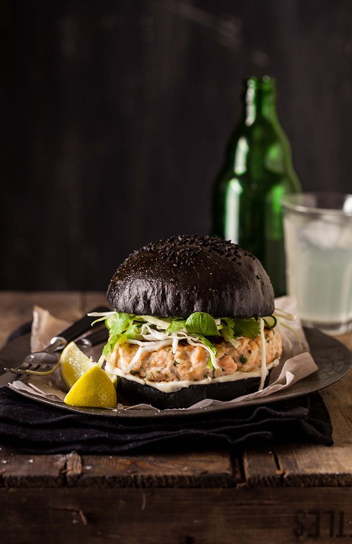 Salmon burger on a black, squid ink brioche bun
