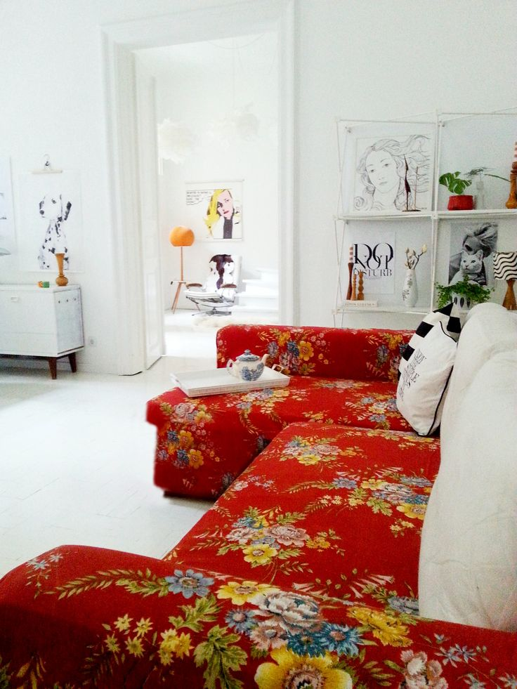 This stunning red floral sofa looks amazing in a neutral white apartment.