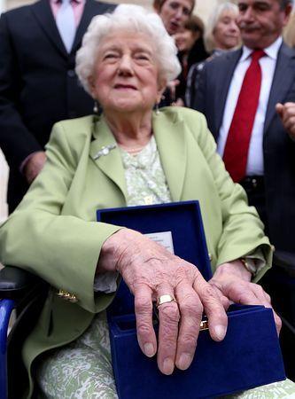 9日、ティラナのアルバニア国防省で、戻った結婚指輪を手にはめたドロシー・ウェブスターさん(AFP=時事) ▼10Mar2015時事通信|結婚指輪、70年経て英遺族に=第2次大戦中、アルバニアで墜落 http://www.jiji.com/jc/zc?k=201503/2015031000145