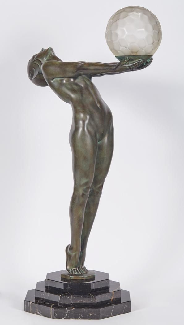 <b>Pair of Art Deco Green Style Patinated-Bronze Figural Lamps </b> <br /> Max LeVerrier, modern <br /> Each standard in the form of a young woman standing on her toes and leaning backwards with her arms extended forward and carrying a shallow bowl as an offering, molded frosted glass honeycomb globe shade, on a stepped octagonal Portor marble base. <i>Height overall 33 inches, height of shade 5 1/4 inches.</i> <br /> <br /> C