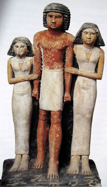 """Grupo de Mersuankh con sus dos hijas. reino Antiguo, V Dinastía. El Cairo, Museo Egipcio. Mersuankh muestra la captación del impulso previo al movimiento del personaje, rompiéndose la inmovilidad del conjunto. La postura de hombros y brazos con los puños cerrados, modelo que persurará también a través del arte griego con los """"kouros""""."""