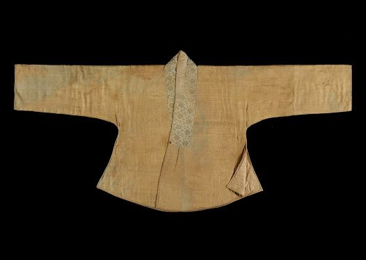 """A long Jeogori excavated from Lady Kim of Gangneung (region), died at age 38. She is assumed to be a person lived in 1520's. It is a padded winter clothes with lotus and auspicious patterned silk fabric on the outer layer. The length of Git (collar) is same on each side and there are gathers under the point that collars meet. It must have been worn as an outer garment over a short Jeogori."" At the Seok Juseon Memorial Museum, Dankook University, via the Google Cultural Institute."