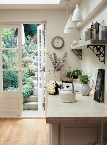 Observe a iluminação desta cozinha. Que beleza! Portas francesas, com boa parte da folha de vidro, dando passagem direta para o jardim/horta. Isto nos dias de hoje é um privilégio.