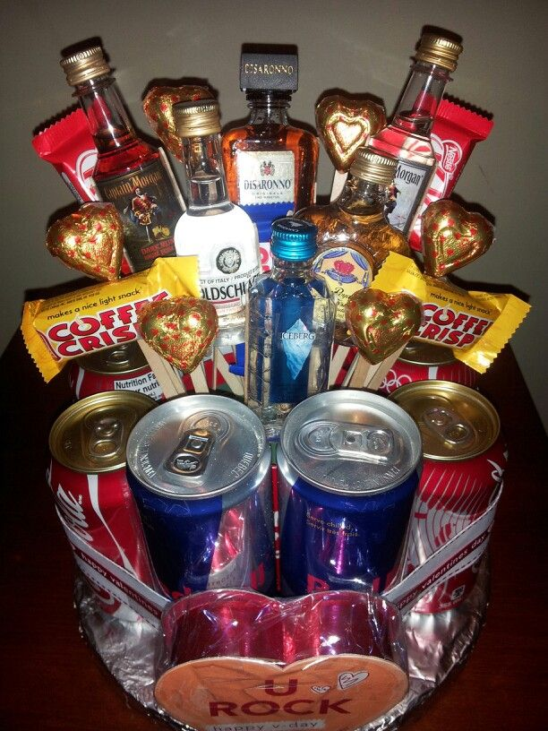 Men's Valentines Candy and Liquor Bouquet Cake featuring six mini bottles, Red Bull,  Coca Cola and chocolate treats.   For more information, visit us on Facebook!   Facebook.com/MemorablySweetArrangementsandGifts