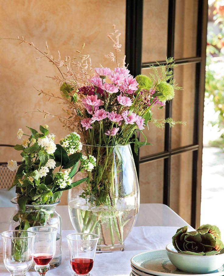 Muy natural  Platos azules de loza y copas de cristal de Aquitania. Flores de Hortícola Balear.