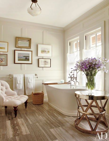 A neutral and bright bathroom with a free standing tub | archdigest.com