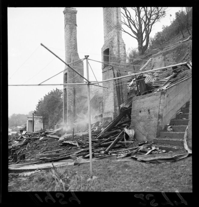 Site (?) of a house fire in Brooklyn, Wellington, showing smoking debris and brick chimneys 27 July 1959
