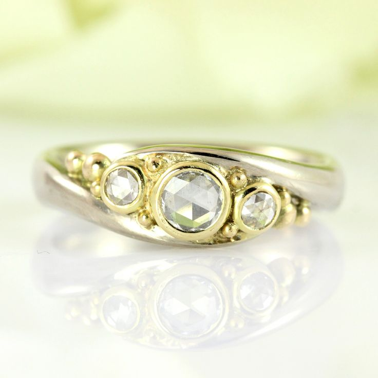 """Split ring of white gold with romantic rose-cut diamonds, mounted in 18k yellow gold and surrounded by cheerful bubbles. This is the old-fashioned way of cutting stones - before the diamond cut became """"come il faut"""" and it provides a unique """"old world"""" look. Created as an engagement ring. Also comes in a simpler version without bubbles."""