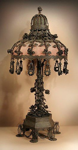 "Steampunk ""THE ROSE GARDEN"": A handmade iron table lamp with matching shade. Wire cages stand on the feet of the base, connected by chains. In the stem are dozens of thorned vines and roses. The shade has rose stems trailing down to its rim to oval shaped drops, each with a sparkling jewel center."