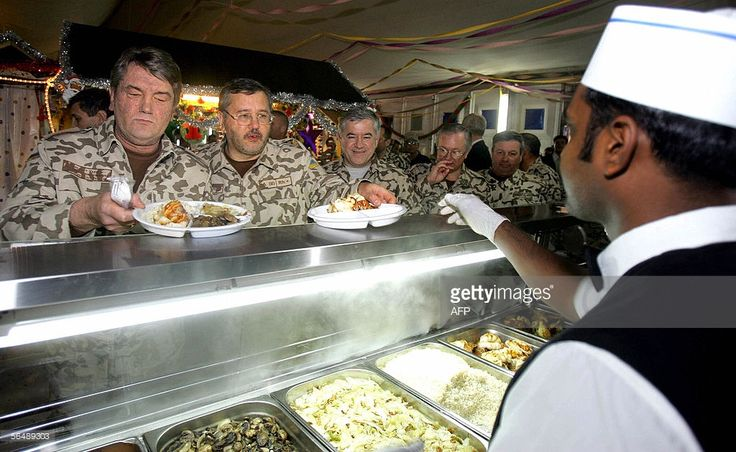 President of Ukraine Viktor Yushchenko, Minister of Defence Anatoly Hrytsenko, Head of National Security and Defence Council Anatoly Kinakh, and Foreign Minister Boris Tarasyuk have dinner at a military base near the Shiite city of Kut, where Ukrainian troops have been stationed, 26 December 2005. Ukraine President Viktor Yushchenko arrived in Iraq on Monday for a surprise visit, as Ukraine wrapped up a withdrawal of most of its troops from the country. Yushchenko ordered Ukraine's troops…