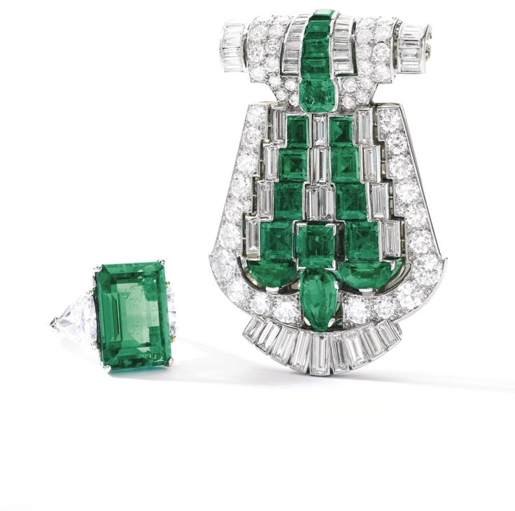 Emerald and diamond clip, Cartier, 1930s Of geometric and open work design, set with variously shaped emeralds, and circular-cut and baguette diamonds, signed Cartier, numbered, case stamped Cartier.