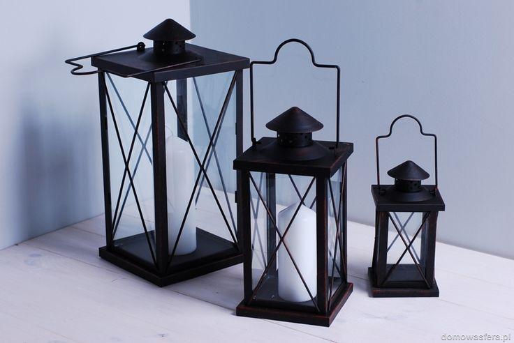 Komplet trzech metalowych lampionów ze szklanymi ściankami. Latarnie pokryte są ciemną patynową farbą w odcieniu brązowym. Dzięki metalowym daszkom, do lampionów można włożyć duże świece. Gwarantujemy, że wniosą niepowtarzalny klimat do wnętrza Twojego domu.