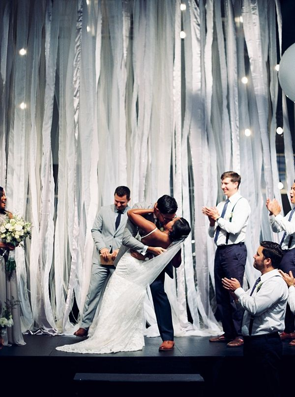 Gorgeous industrial wedding ceremony backdrop of silver streamers and giant white balloons