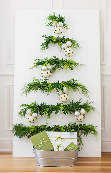 Branch out with an unconventional, space-saving wall tree. Get the scent and feel of a real tree in a fraction of the space by fastening greenery to a panel. A galvanized buckets puts presents on display.