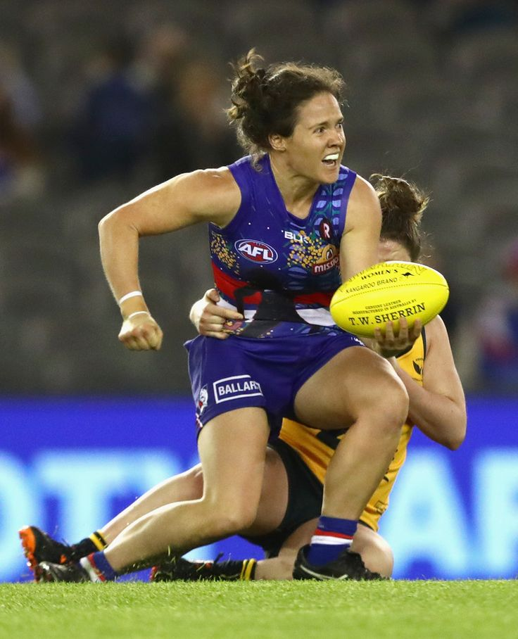 Emma Kearney of the Bulldogs handballs whilst being tackled by Lara Filocamo of Western Australia during the Western Bulldogs v West Australia Women's Exhibition match before the round 11 AFL match between the Western Bulldogs and the West Coast Eagles at Etihad Stadium on June 5, 2016 in Melbourne, Australia.