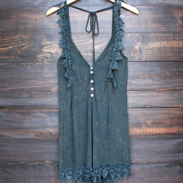 This ultra-soft vintage inspired navy cotton blend romper features an acid wash finish, a button-up front, crochet lace hem detailing, and an open back. Unlined, opaque. - imported - cotton/spandex/po