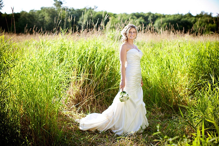 Beautiful bride in sunny field of grass