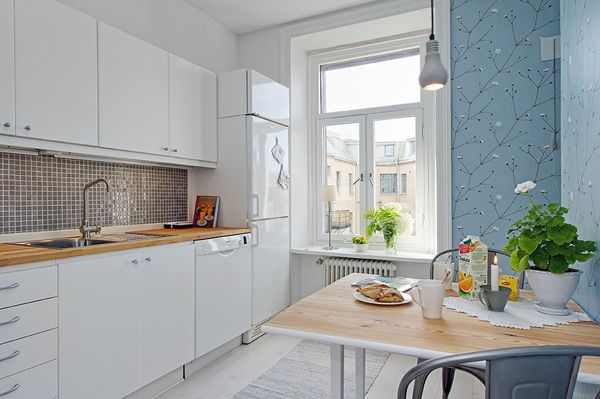 biała kuchnia z tapetą niebieska na ścianie i metalowymi industrialnymi…