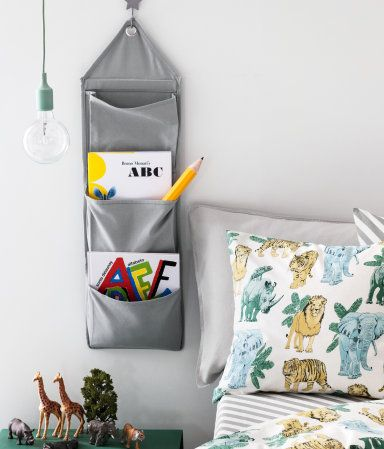 Wall-hung canvas organizer with three pockets. Grommet at top for easy attachment to wall. Size 10 1/2 x 37 1/2 in.