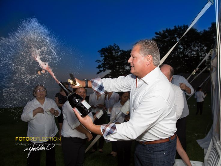 Groom popping champagne with machete.