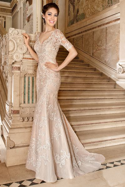 1488 This sophisticated form fitting gown is entirely embellished with venise lace and features a v-neckline and short sleeves. The striking sheer lace back features buttons and is finished with a sweep train.
