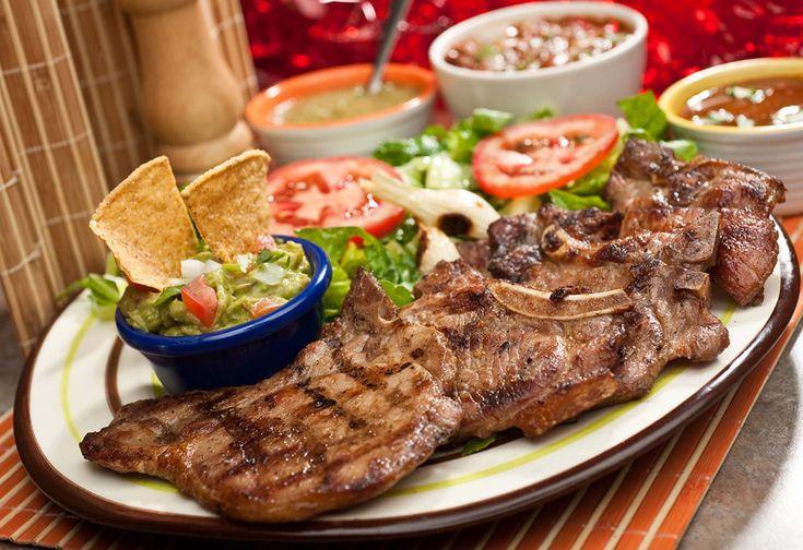 Chuletas asadas a la parrilla (Arranchera al Tequila) acompañadas de ensalada y Guacamoles. Gastronomia de Monterrey, Mexico.
