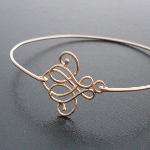 A gold plated curly cue design has been transformed into a delicate bangle with brass band.    Also available in gold plated band.    This stacking ba
