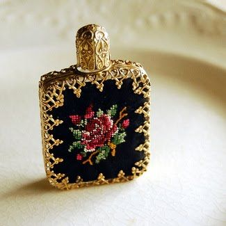 A beautiful petit-point rose graces the front of this vintage perfume bottle