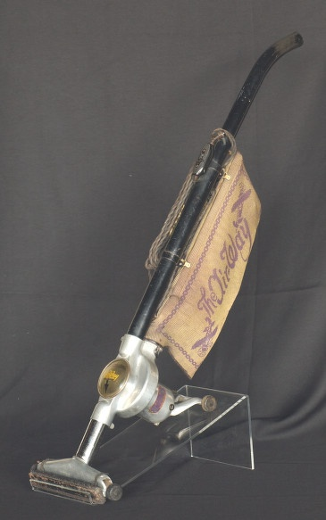 This 1926 vacuum cleaner was manufactured by Air-Way Sanitizor of Toledo, Ohio. It includes attachments and a disposable bag.