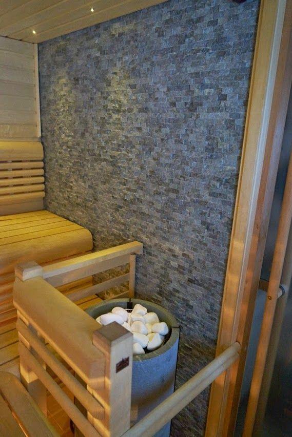 Beautiful sauna in Finland with Tulikivi sauna heater Naava and Tulikivi Natural soapstone mosaic on the wall.