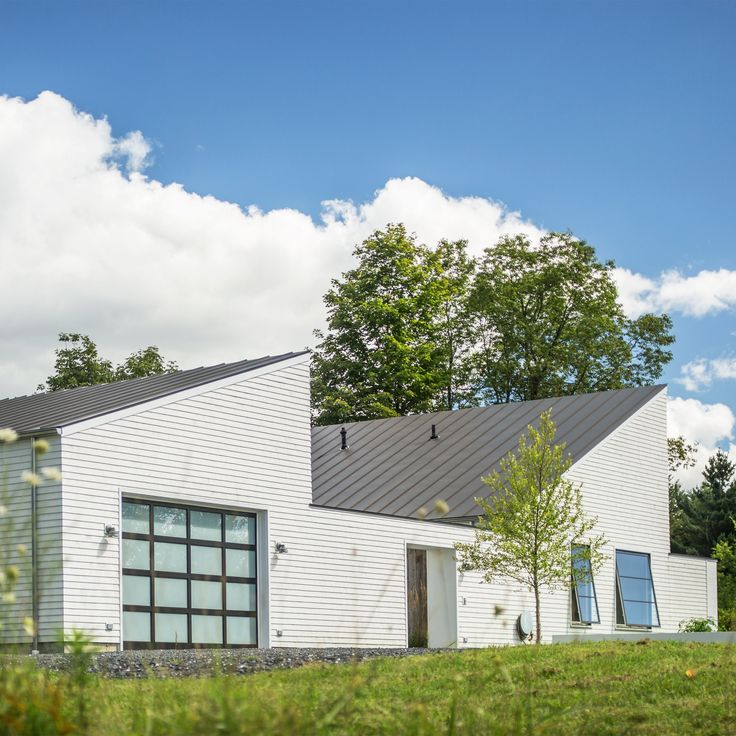 A pair of buildings with pitched roofs and white-washed exteriors form this home in rural Vermont by design-build studio Birdseye Design.