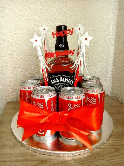 """BOOZEDAY CAKE Made this for my son. Used bottle of Jack, 8 cans of Coke, 3"""" round oasis holder, oasis off-cuts, 4 bamboo skewers, 11"""" cake board, ribbon to tie round and finish off. Glue oasis holder to centre of cake board and place bottle in holder and wedge oasis off-cuts around sides to secure. Glue cans around holder. Push decorated skewers into oasis. Tie ribbon around."""