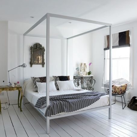 """""""The combination of a sleek white metal bed frame, an ornate gilt mirror, an industrial table lamp, and a painted wood floor make for an appealing eclectic modern bedroom. Put together a similar look with the following elements."""""""