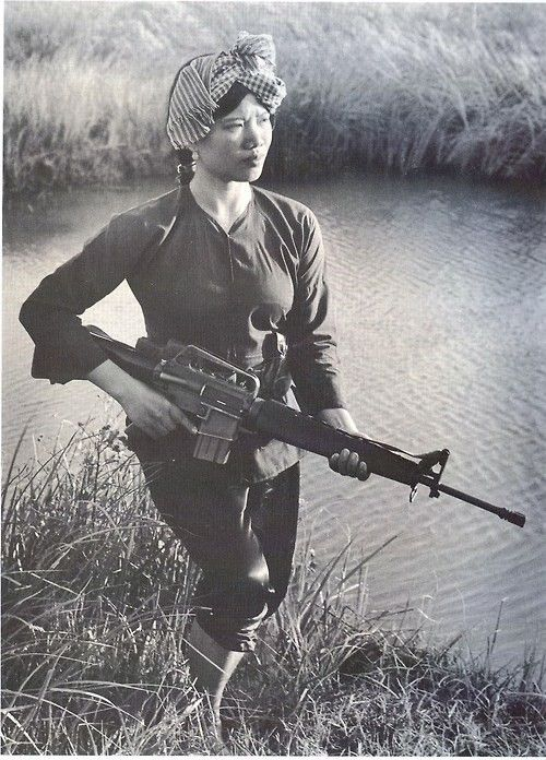 Vietnam War: A female member of South Vietnam's village militia companies goes on patrol with her M-16 at the ready, c.1971.