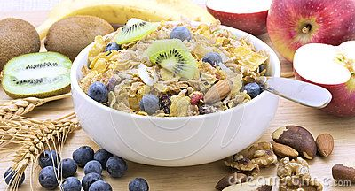 Wholegrain cereal, sliced kiwifruit and blueberries in a white bowl with a spoon. Kiwifruit, apples, wheat, nuts and blueberries surround the bowl.