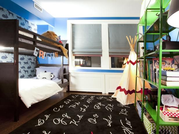Bright and colorful, the boy's bedroom features vibrant blue walls, x-ray animal wallpaper, open green shelves for organization and a playful teepee.